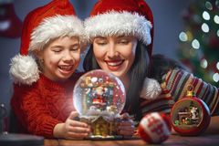 Mom and daughter with snow globe Royalty Free Stock Image