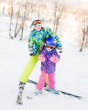 Mom and daughter while snow skiing showing thumbs up Stock Image