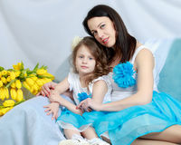 Mom and daughter on the sofa with a bouquet of flowers. Royalty Free Stock Photos