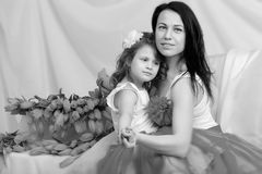 Mom and daughter on the sofa with a bouquet of flowers. Royalty Free Stock Photo