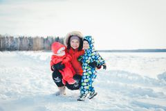 Mom daughter and son hugging on the winter walk on a cold morning stock images