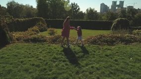 Mom and daughter spend time in the park together. Shot on drone stock video footage