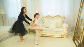 Mom and daughter in splits. Mom ballerina stretches her little daughter in twine stock video footage