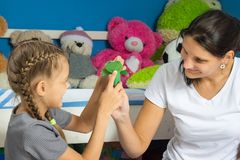 Mom and daughter stick a head to paper finger figurine of a frog stock photography