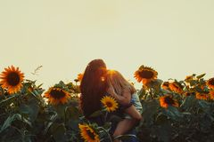 Mom and daughter among sunflowers. Happy mother hugs her daughter in a sunflower field Stock Images