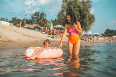 Mom and daughter swiming on an inflatable donut stock photography