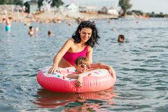 Mom and daughter swiming on an inflatable donut royalty free stock photo
