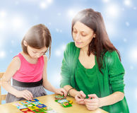 Mom and daughter at the table playing educational games Royalty Free Stock Photography