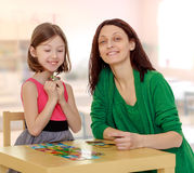 Mom and daughter at the table playing educational games Stock Photo