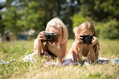 Mom and daughter taking pictures lying on blanket in park. Mother and child girl pretending to be photographers Stock Photography
