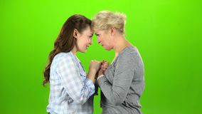 Mom and daughter talking on various topics. Green screen. Side view. Mom and daughter stand and talking on various topics. Green screen. Side view stock video