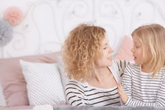Mom and daughter talking. Young mom and her little daughter talking in a bedroom stock images