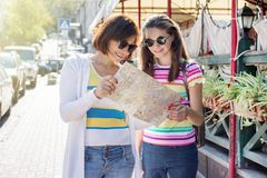 Mom and daughter teenager tourist looking at the map on the stre Royalty Free Stock Images