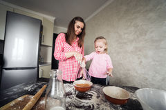 Mom and daughter together in the kitchen Stock Photography