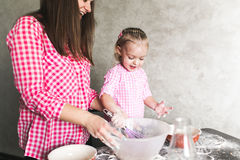 Mom and daughter together in the kitchen Stock Photos