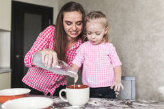 Mom and daughter together in the kitchen Stock Images