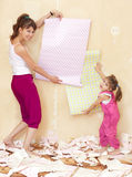 Mom and daughter try on wallpaper Royalty Free Stock Image