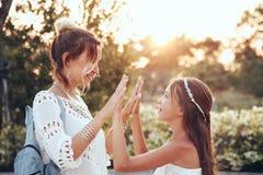 Mom with daughter. Tween daughter holding hands her mom in summer sunlight Stock Photo