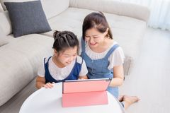 Mom and daughter use tablet happily royalty free stock photography