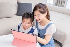 Mom and daughter use tablet happily stock photos