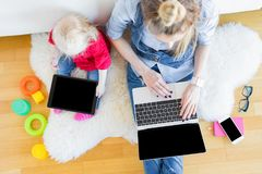 Mom and daughter using tech gadgets together. While sitting on floor Stock Images