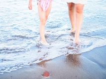Mom and daughter wading in water on sandy beach. A mom and a daughter wading in the water on a sandy beach Royalty Free Stock Image