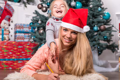 Mom and daughter waiting for Christmas Stock Photography