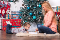 Mom and daughter waiting for Christmas Royalty Free Stock Image