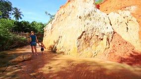 Mom Daughter Walk along Stream Turn Around Sunny Cliff stock video footage
