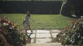 Mom and daughter walk in the park. Slow motion stock video footage
