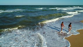 Walk along the seashore. Mom and daughter walk through the waves along the seashore stock footage