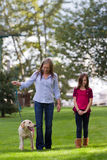 Mom And daughter walking the dog Royalty Free Stock Photo