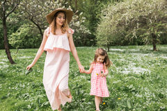 Mom and daughter are walking in garden. Mom and daughter are walking in the park Stock Image