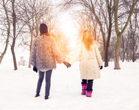 Mom and daughter walking in the snow by the hand Royalty Free Stock Photos