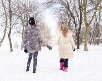 Mom and daughter walking in the snow by the hand Royalty Free Stock Images