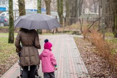Mom and daughter   walking together with stroller Royalty Free Stock Photos