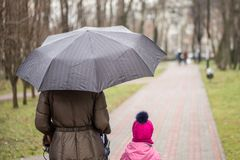 Mom and daughter   walking together with stroller Stock Photos
