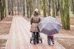 Mom and daughter   walking together with stroller Stock Images