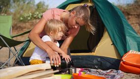 Mom and daughter want to get warm with hot tea during camping trip stock video