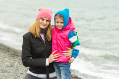 Mom and daughter in warm clothes hugging each other on the beach in cold weather and with a smile look Stock Photos