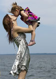 Mom and Daughter by the water. A young mom kisses her daughter by the water royalty free stock photography