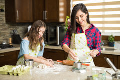 Mom and daughter weighing some dough. Pretty young women and her daughter kneading some cookie dough and weighing it before baking Stock Image