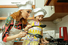 Mom and daughter in white chef hats cook in the kitchen. Stock Image