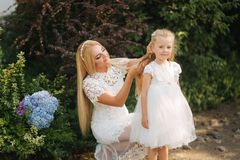 Mom with daughter in white dresses spend time in the park. Blond hair female. Mother weaves pigtails daughter outside.  stock photos