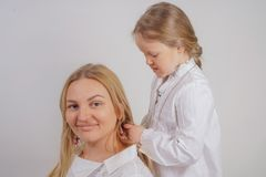 Mom and daughter in white shirts with long blonde hair posing on a solid background in the Studio. a charming family takes care of. Each other and makes braids royalty free stock photo