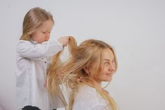 Mom and daughter in white shirts with long blonde hair posing on a solid background in the Studio. a charming family takes care of. Each other and makes braids royalty free stock image