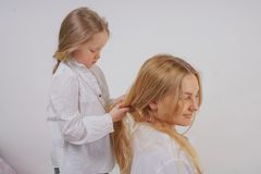 Mom and daughter in white shirts with long blonde hair posing on a solid background in the Studio. a charming family takes care of. Each other and makes braids royalty free stock images