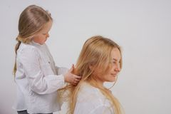 Mom and daughter in white shirts with long blonde hair posing on a solid background in the Studio. a charming family takes care of. Each other and makes braids stock image