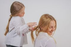 Mom and daughter in white shirts with long blonde hair posing on a solid background in the Studio. a charming family takes care of. Each other and makes braids stock photography