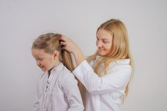 Mom and daughter in white shirts with long blonde hair posing on a solid background in the Studio. a charming family takes care of. Each other and makes braids stock photo